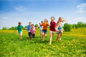 a group of children running together in a field grass