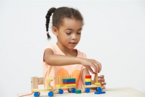 little girl playing wooden toys