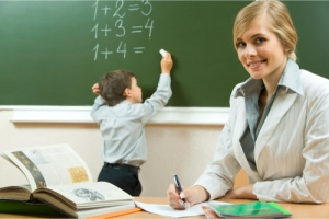 portrait of a smiling teacher while her student is solving an equation on the board